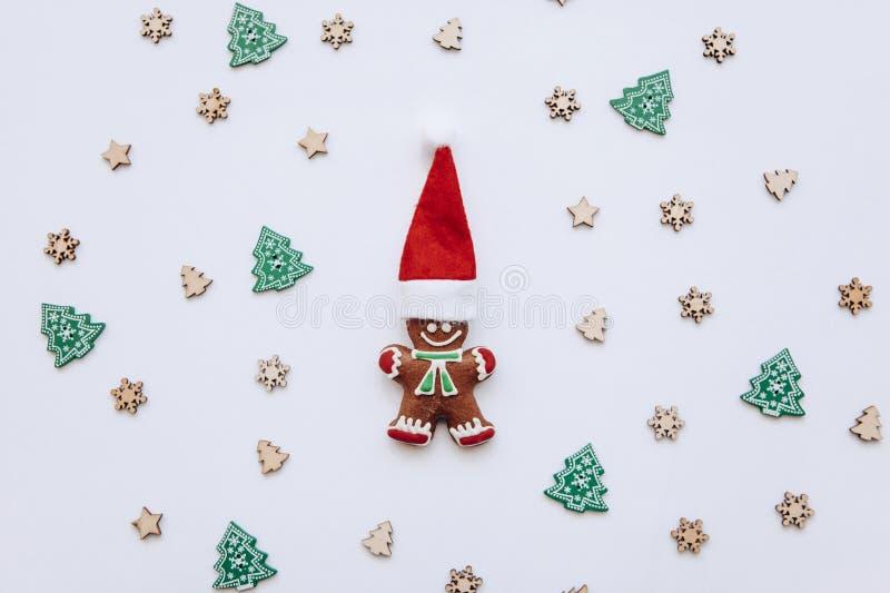 Pan de jengibre de la Navidad bajo la forma de pequeño hombre del jengibre en un sombrero tradicional rojo en un fondo festivo ad imagen de archivo