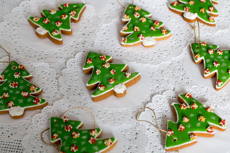 Pan de jengibre pintado en la forma del árbol de navidad en un fondo blanco de la servilleta Galletas de los árboles de navidad - foto de archivo