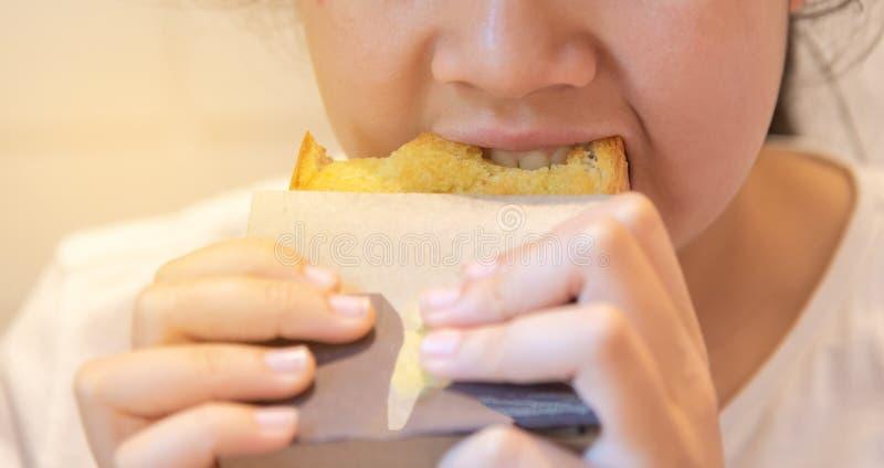 pan de la mantequilla de la muchacha del adolescente que muerde foto de archivo libre de regalías