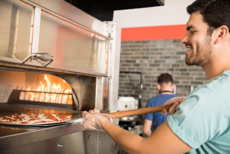 Pan de la pizza de la hornada del cocinero en horno en la cocina comercial foto de archivo libre de regalías