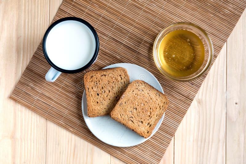 Pan de la tostada con Tin Mug de la leche y del tarro de miel fotos de archivo libres de regalías