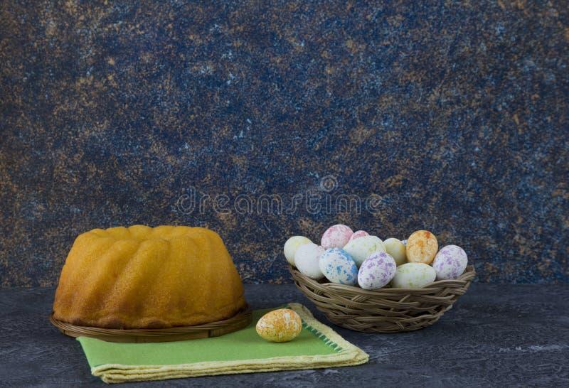 Pan de Pascua y mini huevos de Pascua en una pequeña cesta en la tabla de piedra oscura imágenes de archivo libres de regalías