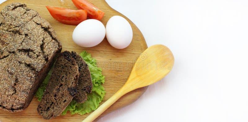 Pan de Rye con las hojas de la ensalada, los huevos, el tomate y la cuchara de madera en la tabla de cortar con el espacio libre  fotografía de archivo libre de regalías