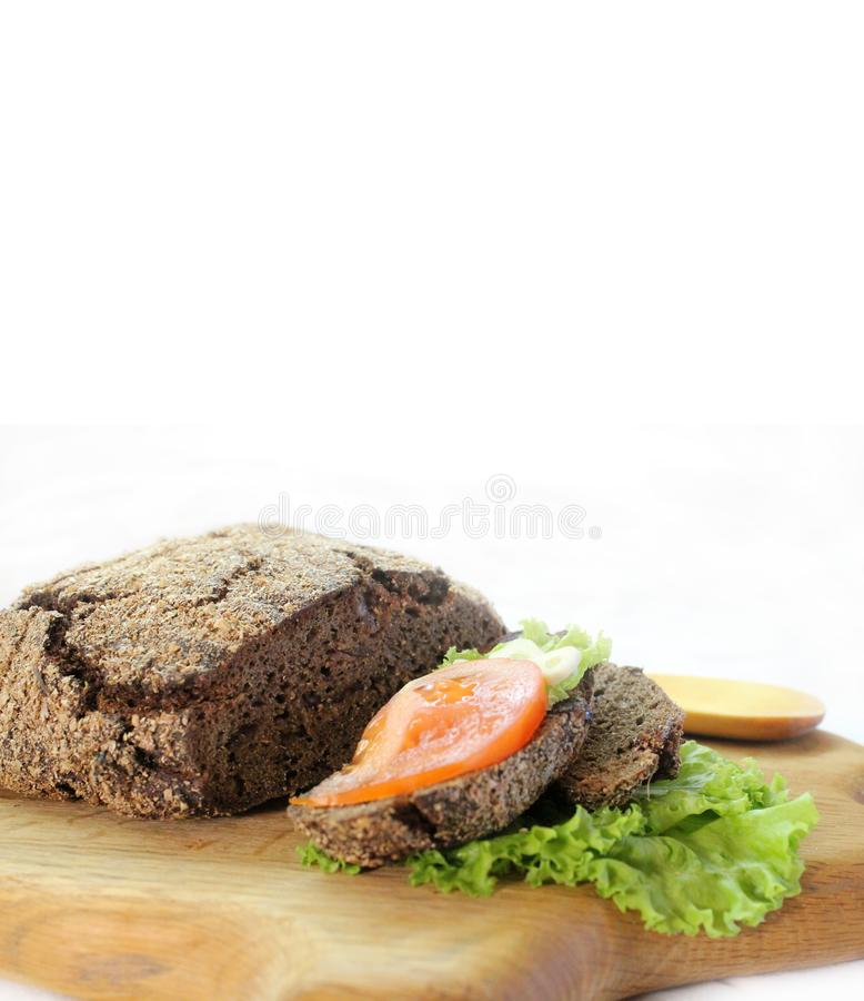 Pan de Rye con las hojas y el tomate de la ensalada en una tabla de cortar con el espacio libre para el texto imagen de archivo