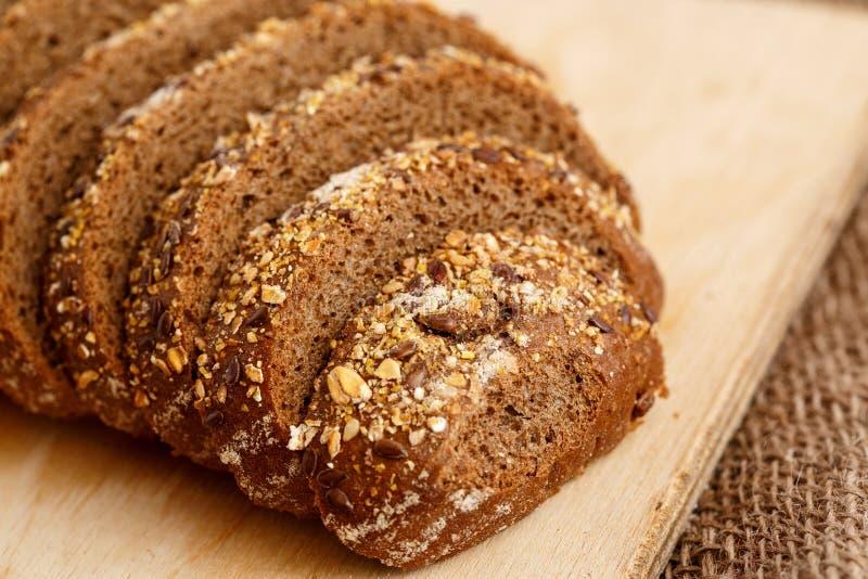Pan de Rye con los granos de cereales en un soporte de madera en un fondo de madera con el espacio para el texto fotografía de archivo