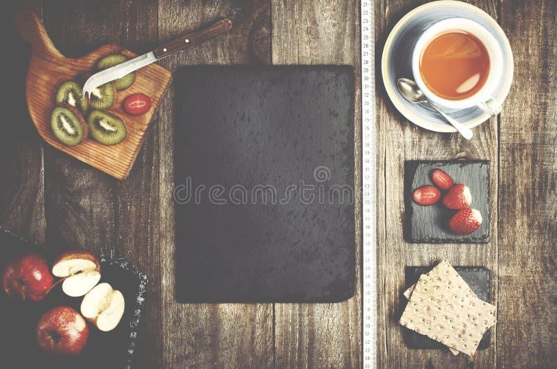 Pan del arroz, té y frutas sanas en fondo de madera E negra imagen de archivo