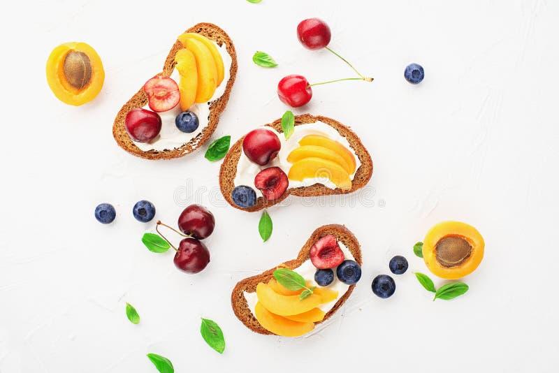 Pan del bocado de la tostada del verano, albaricoques, arándanos, cerezas, hojas de la albahaca, queso cuajado, crema agria, miel imágenes de archivo libres de regalías