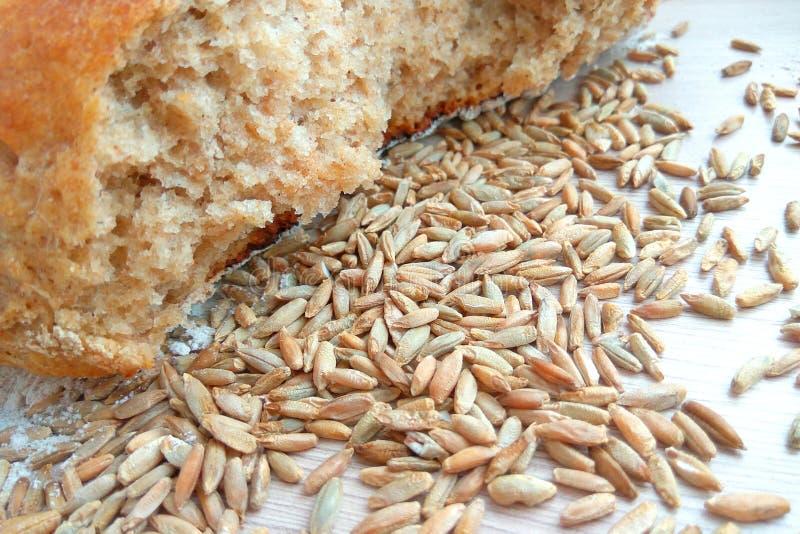 Pan del pan cocido fresco del trigo y de centeno con los granos en fondo de madera de la tabla imágenes de archivo libres de regalías