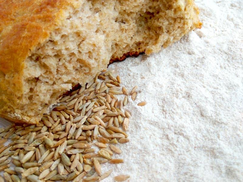 Pan del pan cocido fresco del trigo y de centeno con los granos y harina blanca en fondo de madera de la tabla imagen de archivo
