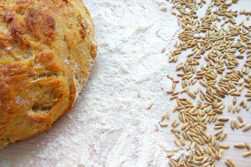 Pan del pan cocido fresco del trigo y de centeno con los granos y harina blanca en fondo de madera de la tabla fotos de archivo