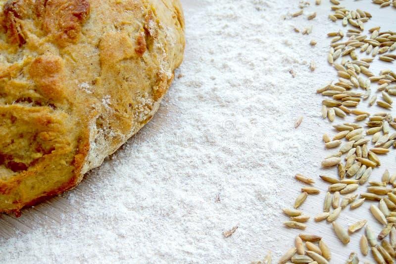 Pan del pan cocido fresco del trigo y de centeno con los granos y harina blanca en fondo de madera de la tabla foto de archivo