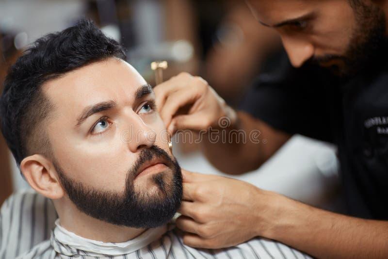 Pan del corte del peluquero con la maquinilla de afeitar para el cliente imagen de archivo