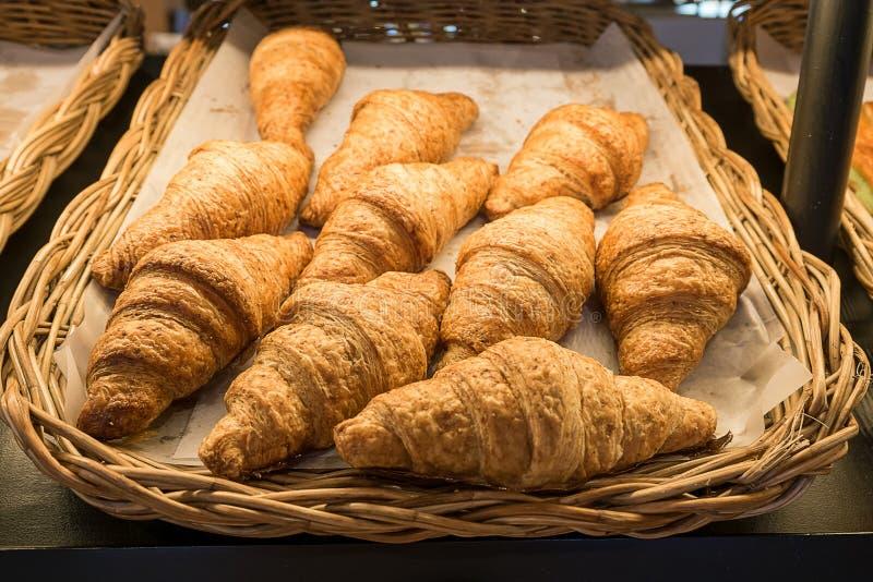 Pan del cruasán en la línea de la comida fría, cruasanes frescos en cesta de mimbre imagenes de archivo