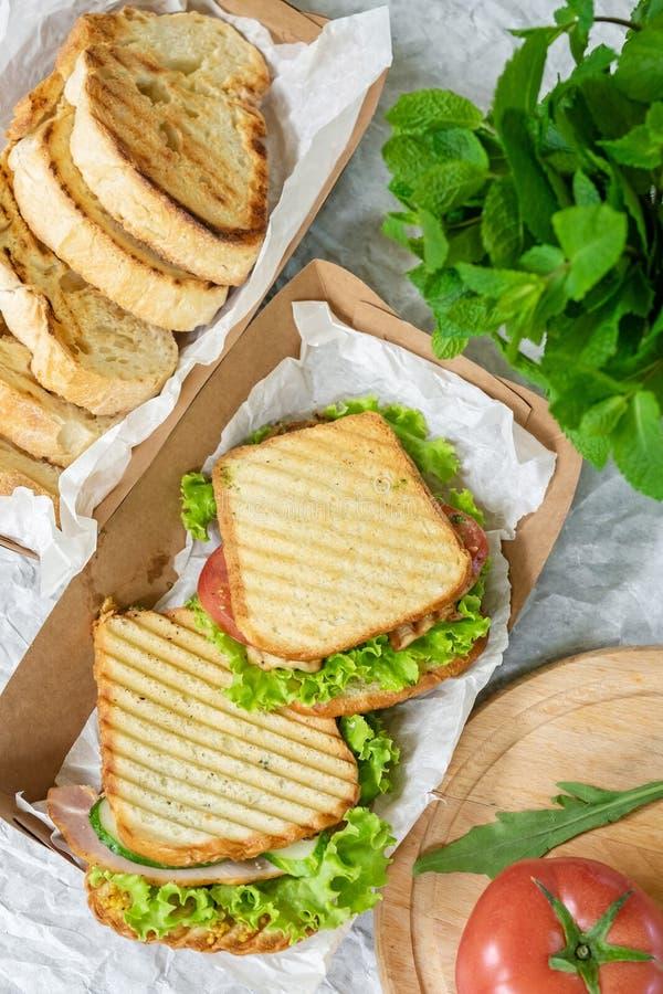 Pan del jam?n con la ensalada y el tomate vegetales en una tabla y un papel imagenes de archivo