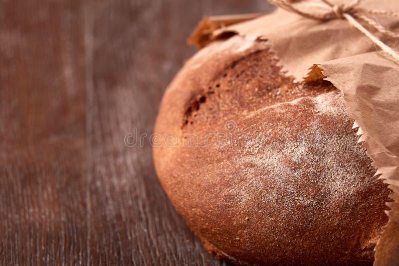 Pan del pan de centeno en bolsa de papel en la tabla de madera Fondo de la panadería imagenes de archivo