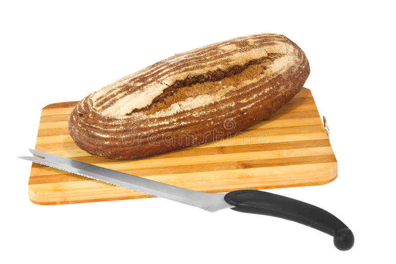 Pan del pan de centeno en un tablero de madera con un cuchillo imagen de archivo libre de regalías
