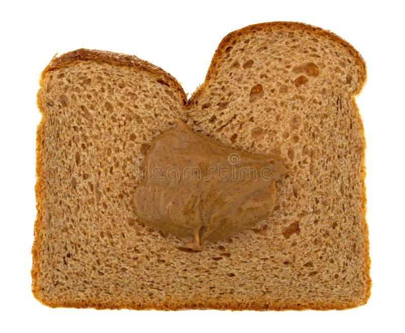Pan del trigo con una gota de la mantequilla de la almendra y de coco aislada en un fondo blanco imagenes de archivo