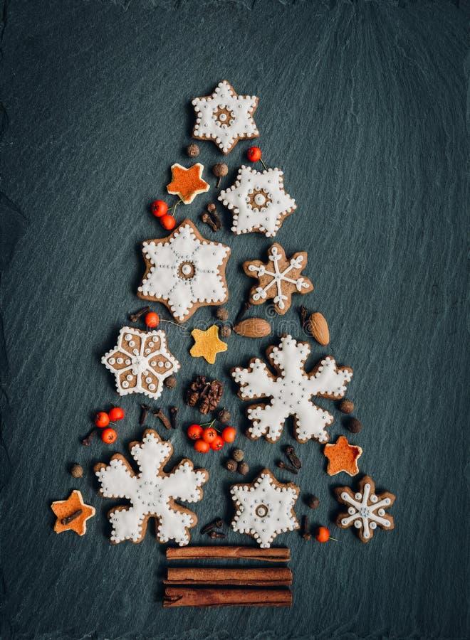 Pan di zenzero, dadi, spezie, scorza d'arancia secca creare un albero di Natale su un fondo di pietra scuro immagine stock libera da diritti