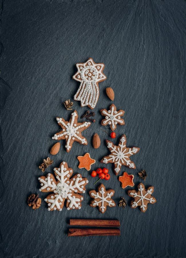Pan di zenzero, dadi, spezie, scorza d'arancia secca creare un albero di Natale su un fondo di pietra scuro fotografia stock libera da diritti
