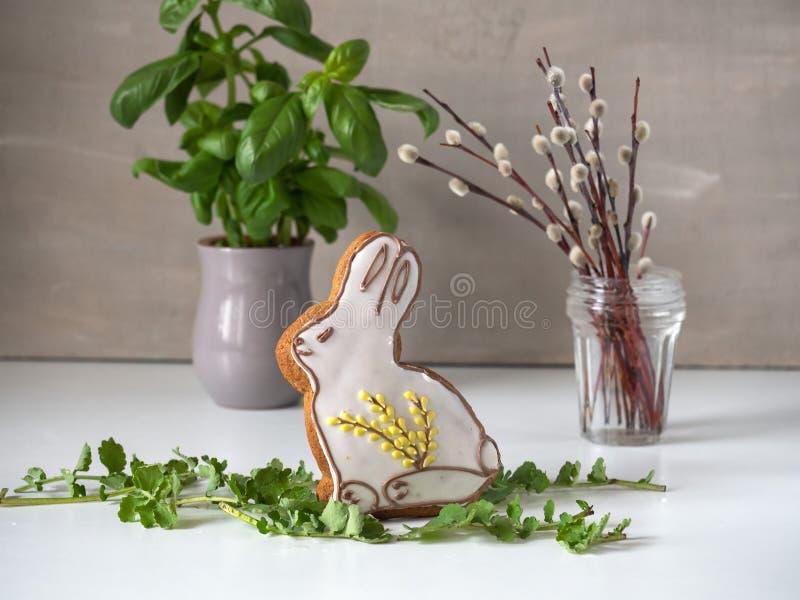 Pan di zenzero di Pasqua, basilico fresco in un vaso ceramico e un piccolo mazzo dei rami del palissandro fotografia stock libera da diritti