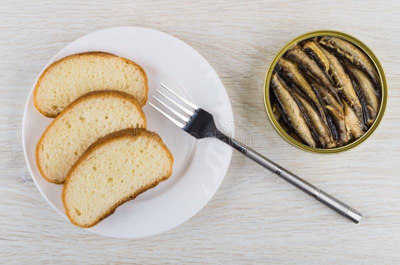 Pan en la placa, espadines conservados en el tarro metálico, bifurcación fotos de archivo libres de regalías