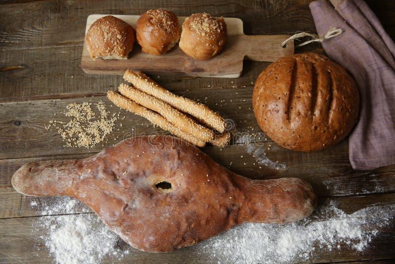Pan en una tabla rústica de madera, bollos del pan en un tablero de madera y las barras de pan con las semillas de sésamo con el  foto de archivo libre de regalías