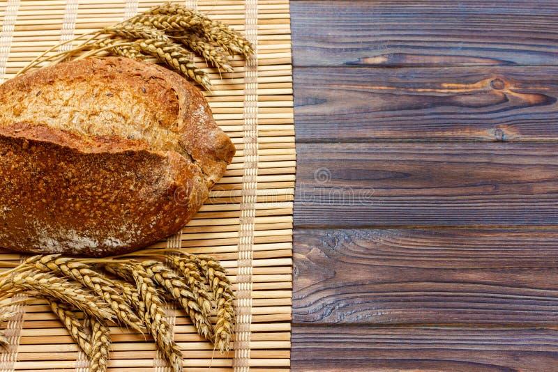 Pan entero hecho en casa fresco con trigo en un fondo de madera fotografía de archivo libre de regalías