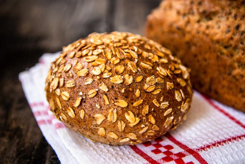 Pan entero orgánico recientemente cocido sano hecho en casa del grano con las semillas sanas en la tabla de madera imagen de archivo libre de regalías