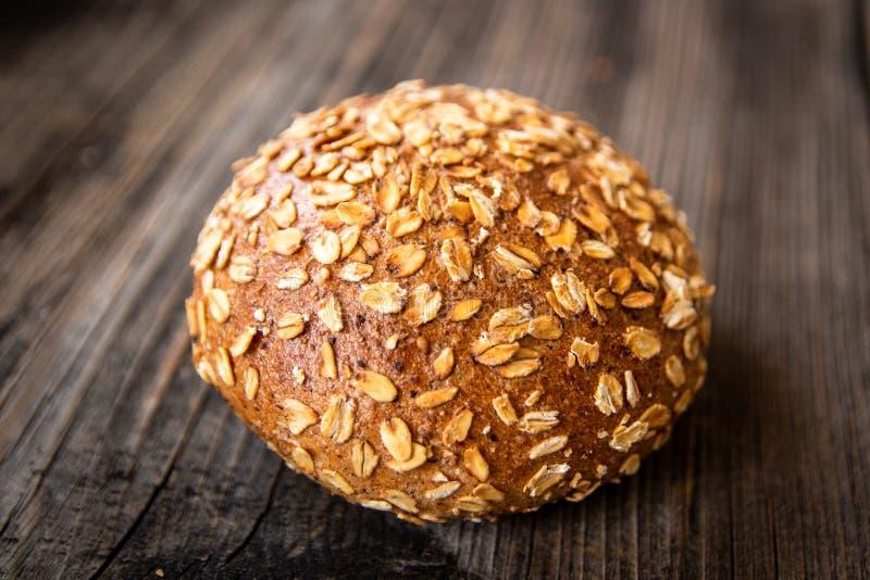 Pan entero orgánico recientemente cocido sano hecho en casa del grano con las semillas sanas en la tabla de madera fotografía de archivo libre de regalías