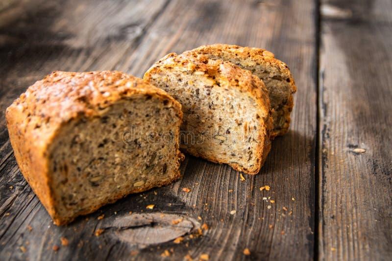 Pan entero orgánico recientemente cocido sano hecho en casa del grano con las semillas sanas en la tabla de madera fotos de archivo libres de regalías
