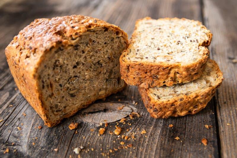 Pan entero orgánico recientemente cocido sano hecho en casa del grano con las semillas sanas en la tabla de madera fotografía de archivo