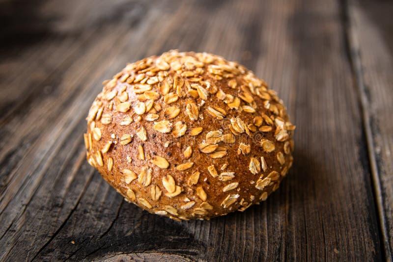 Pan entero orgánico recientemente cocido sano hecho en casa del grano con las semillas sanas en la tabla de madera imagen de archivo
