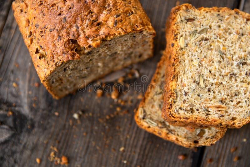 Pan entero orgánico recientemente cocido sano hecho en casa del grano con las semillas sanas en la tabla de madera foto de archivo libre de regalías