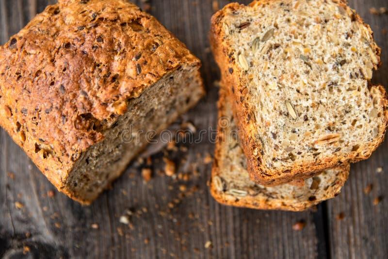 Pan entero orgánico recientemente cocido sano hecho en casa del grano con las semillas sanas en la tabla de madera imagenes de archivo