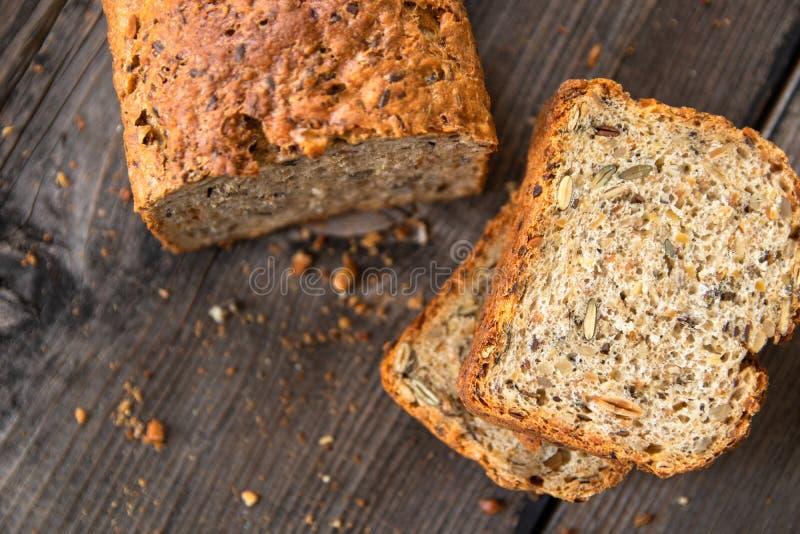 Pan entero orgánico recientemente cocido sano hecho en casa del grano con las semillas sanas en la tabla de madera imágenes de archivo libres de regalías