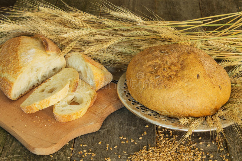 Pan entero y cortado con los oídos y el grano del trigo fotografía de archivo