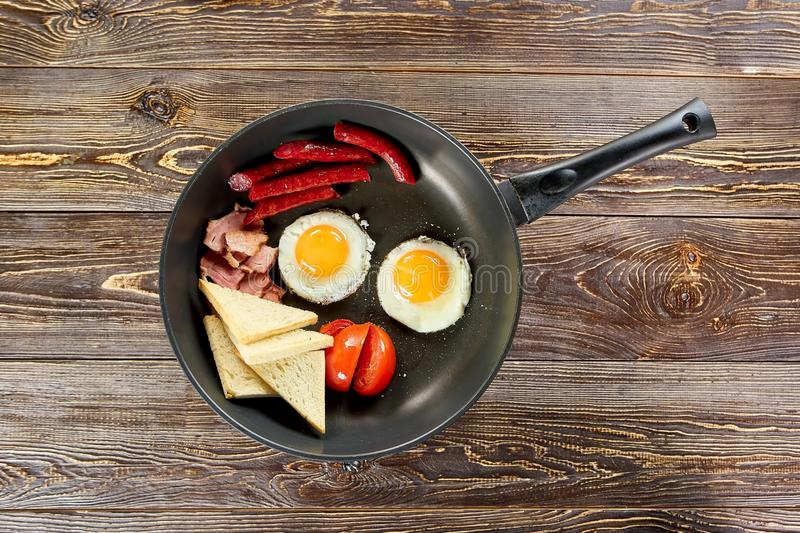 Pan with food, top view. Top view of pan with fried eggs, sausages, ham, tomatoes and bread royalty free stock images