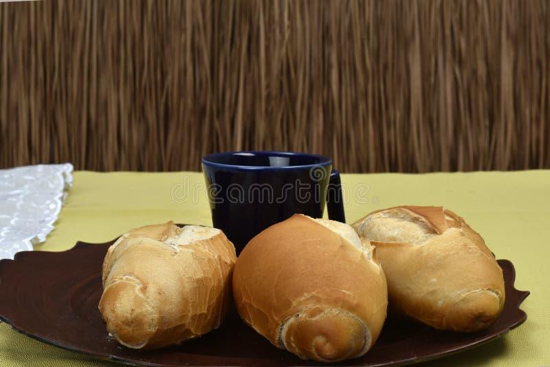 Pan francés en la placa con la taza negra en el fondo imagenes de archivo