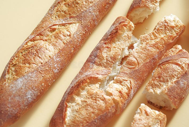 Pan franc?s tradicional Tres baguettes recientemente cocidos que ponen en el contexto amarillo fotos de archivo