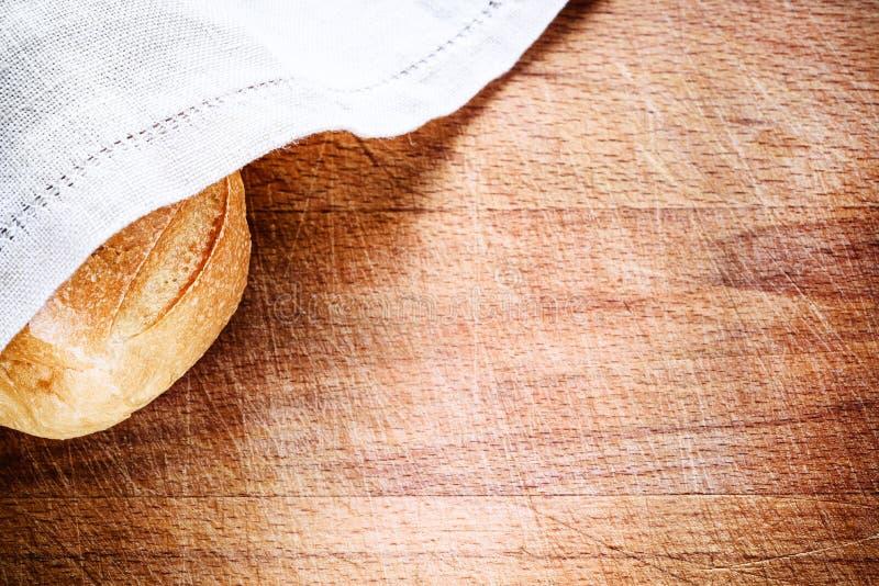 Pan fresco cubierto con la servilleta de lino encima de madera imagen de archivo