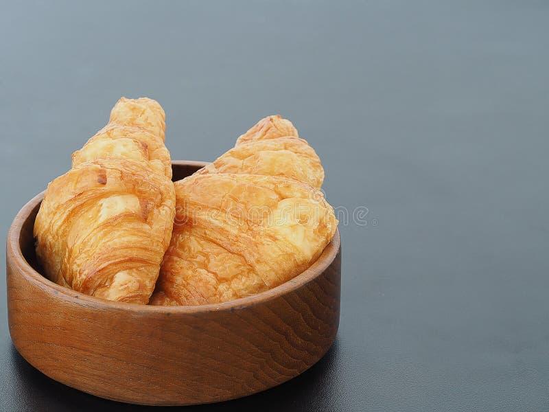 Pan fresco de los cruasanes en el cuenco de madera en la tabla negra en fondo con los spcae de la copia del área para un poco de  imagen de archivo