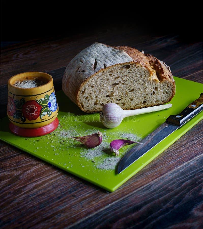 Pan fresco del trigo, ajo, un salero de madera con la sal, un tablero verde para cortar el pan, un cuchillo Todo el esto miente e imágenes de archivo libres de regalías