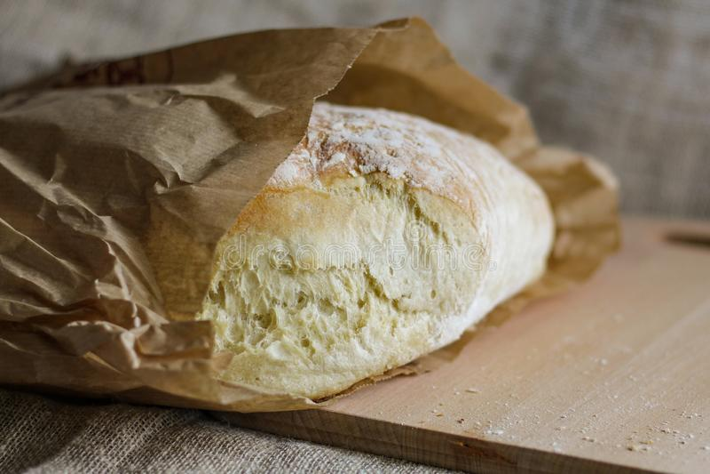 Pan fresco en un tablero del roble envuelto en papel fotos de archivo