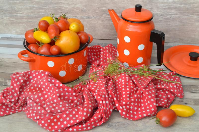 Pan with fresh red, orange and yellow farm tomatoes on the shabby background, red napkin, russian style royalty free stock photos