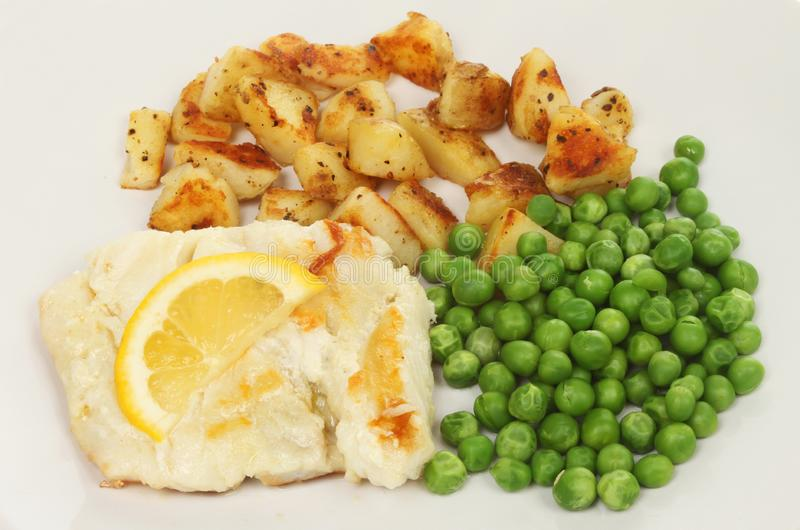 Pan fried cod closeup. Closeup of pan fried cod with saute potatoes and peas royalty free stock photo