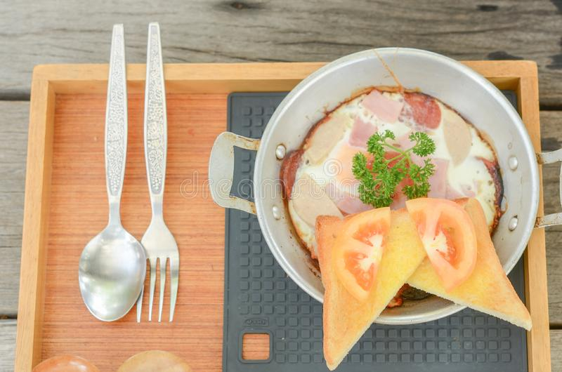 Pan-fried egg with toppings on wooden background. Breakfast food in Thai style. Top view royalty free stock image