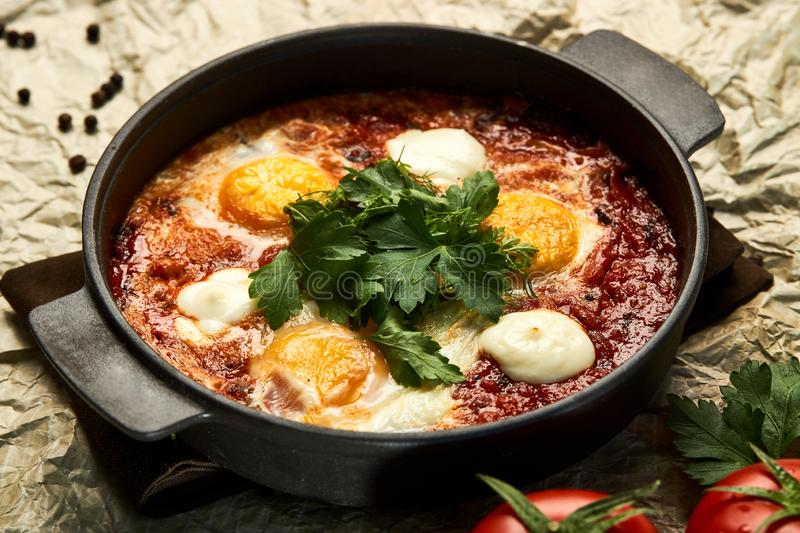 Pan of Fried Eggs with Tomatoes, Sweet Peppers and Coriander. Hot shakshuka with eggs, tomatoes and parsley in a frying pan, close-up. Pan of Fried Eggs with royalty free stock image