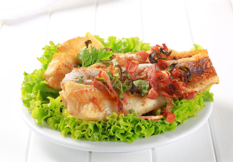 Pan fried fish fillets with bacon bits stock image
