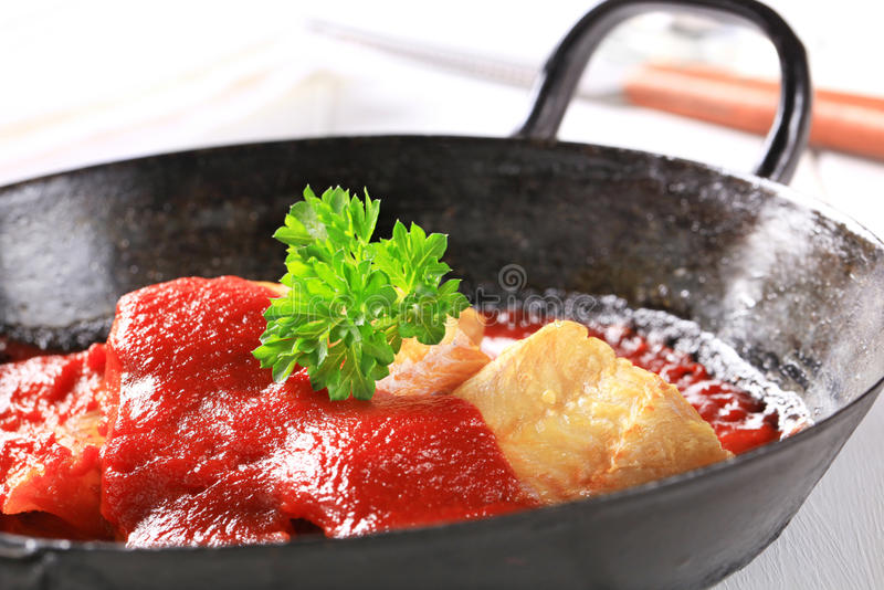 Pan fried fish fillets with tomato sauce stock images