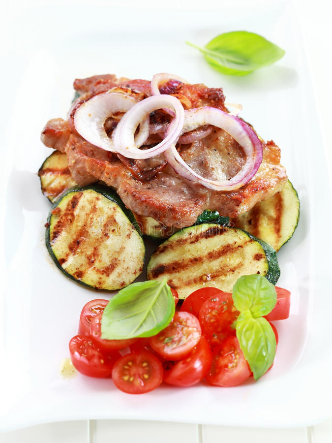 Pan-fried pork steak with grilled vegetable. And tomato salad stock image